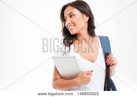 Smiling young asian girl with backpack holding tablet computer and looking away isolated on a white background