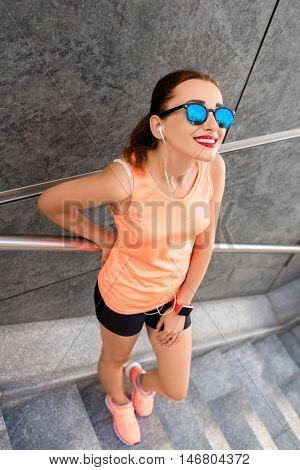 Portrait of a young sports woman near the gray wall on the stairs after morning jogging in the modern city. Healthy lifestyle in the city