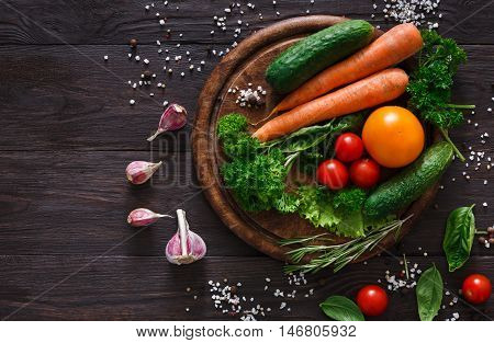 Desk with fresh organic vegetables and greens on wood background. Healthy natural food abundance on rustic wooden table with copy space. Tomato, cucumber, carrot and other cooking ingredients top view