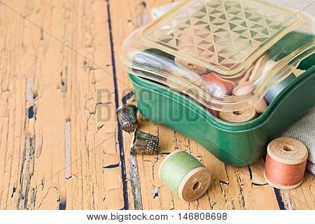 Box with a spools of thread, a piece of fabric and thimbles on an old wooden table.
