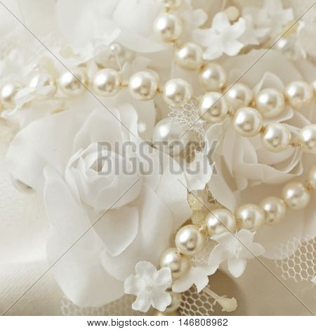 wedding pearls and flowers. pearl necklace on white floral background