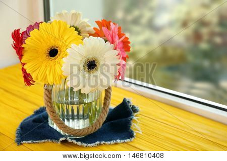 Vase with bouquet of gerbera flowers on window sill