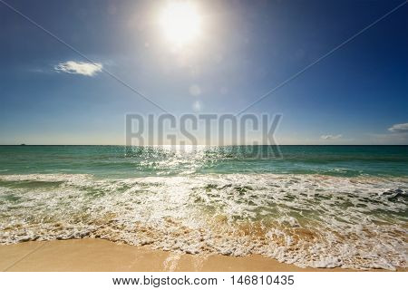 Beautiful beach and waves of Caribean Sea with blue sky and sun. With lens flare