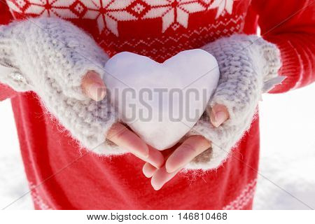 I love winter. Happy winter girl wearing knitted wear holding in hands snow heart. Teenager playing with snowball.