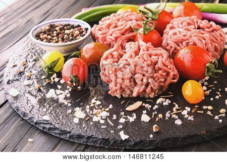 raw minced meat vegetables with salt and spices on a black background selective focus space for text