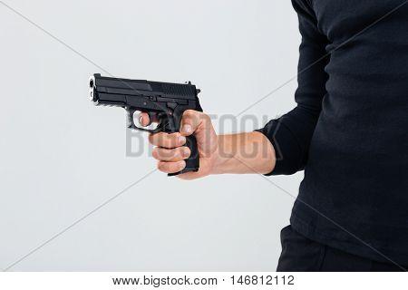Closeup of man in black clothes holding a gun
