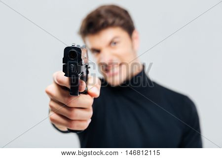 Closeup of angry young man pointing with gun on you
