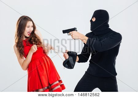 Man theif in balaclava threatening with gun and stealing young woman bag