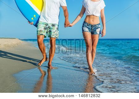 Brasil latino hispanic couple walking holding hands with surfboard and flag as sarong