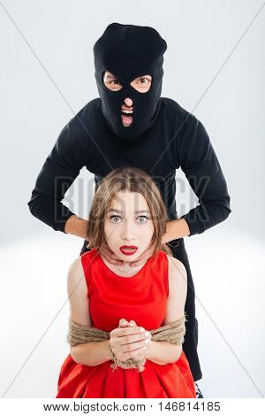 Woman bounded with ropes choking by cryminal man in balaclava
