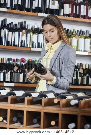 Woman Looking At Wine Bottles In Store