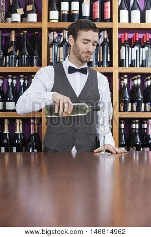 Male Bartender Pouring White Wine In Glass