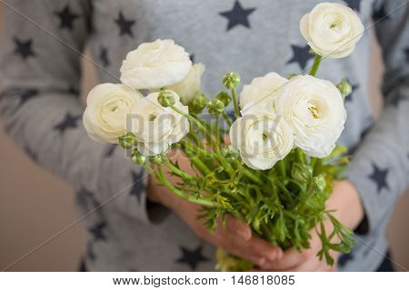Closeup of woman's hands golding a bunch of beautiful white ranunculus. Grild with bouquet of flowers. Ranunculus. Holidays and lifestyle concept