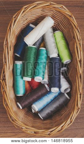 Bobbins thread in willow basket on wooden background