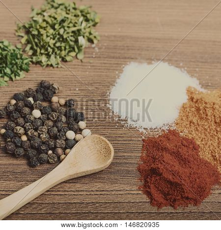 Heaps of spices with wooden spoon