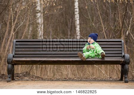 Adorable little toddler boy sitting on a big bench in the park. outdoor walks with children. Child on the park bench.