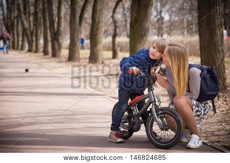 Young beautiful mother talking to her son riding on a small bicycle in the park. Child on the bike on asphalt road. Children activities outdoors. Family walking in the city park.