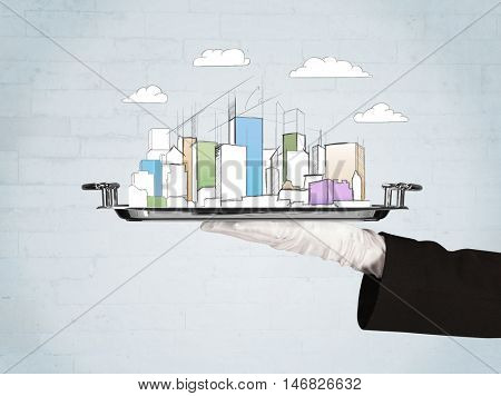 Serving a city concept with close up of waiter hand in gloves holding silver plate in front of grey brick wall