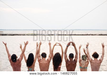 Back view of happy young people sitting with raised hands on pier near the sea