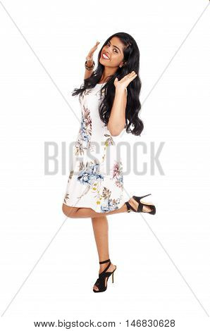 A beautiful young woman dancing in a dress and high heels with her long black hair isolated for white background.