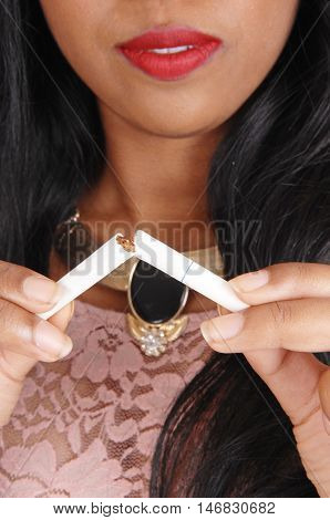A closeup image of the mouth and chest of a young woman breaking a cigarette stop smoking isolated for white background.