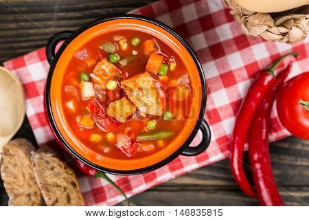 Stew soup with meat and vegetables in the pot - top view