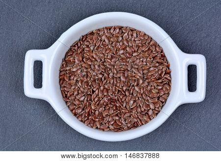 Flax seeds in a ceramic bowl on slate