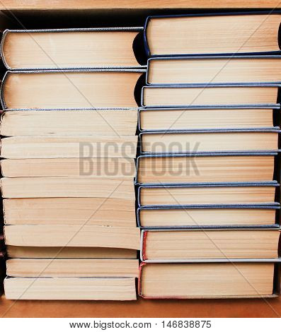 Stacks of various new literature books on the shelf in the library background ready to read