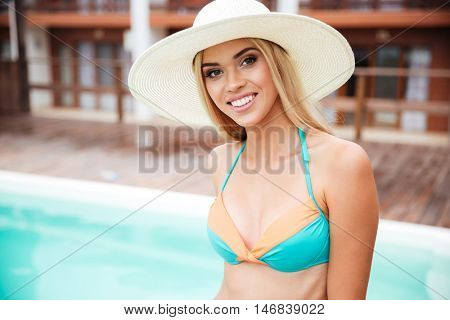 Closeup of cheerful cute young woman in hat standing near swiming pool