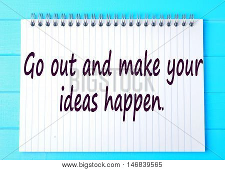 Go out and make your ideas happen words.Inspirational quote on notepad