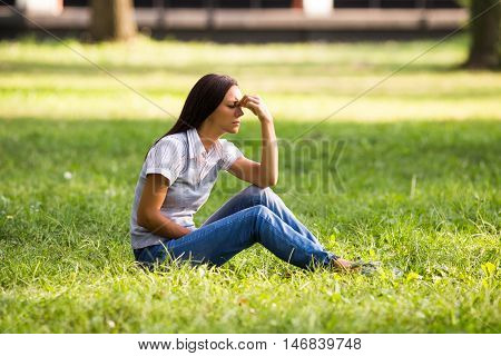 Beautiful businesswoman is sitting at the park and she is having a strong headache.