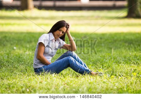 Businesswoman is sitting at the park and she is very depressed because of something.