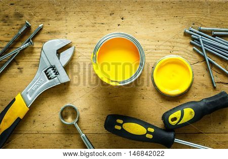 construction tools on a wooden table with yellow paint top view