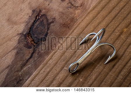 Fish Hook with 3 hooks on a wooden background with a large wood knot