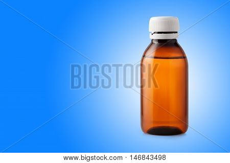 Medicine bottle of brown glass or plastic on blue background with copy space place for text. Medicine bottle without label. Cough syrup
