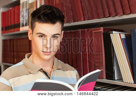 Serious student with open book and bookshelves on background