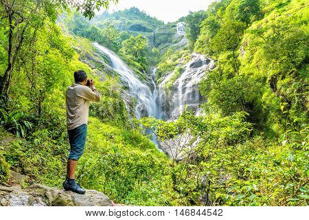 Tourist man is taking photograph heart-shaped waterfall. Pitugro waterfall locate in deep forest of Umpang Thailand.