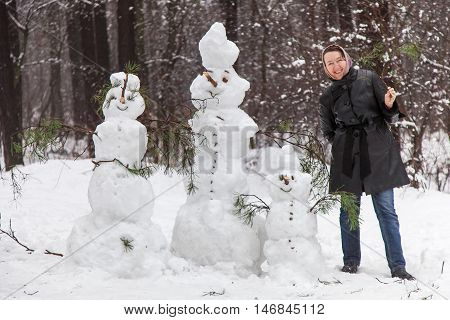 Cheerful woman standing in woods near family of snowmen