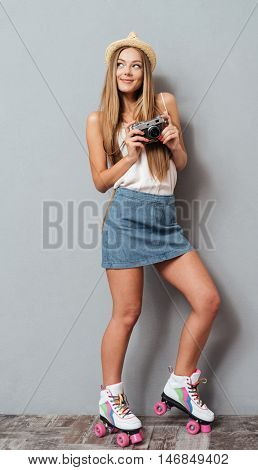 Pretty young girl in hat and roller skates holding photo camera isolated on a gray background