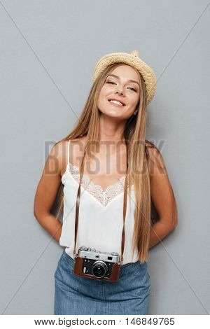 Smiling attractive blonde girl in hat with photo cmera standing isolated on a gray background