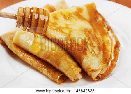 Pancakes with honey syrup on a white plate. Traditional crepe for pancake week or Shrovetide.