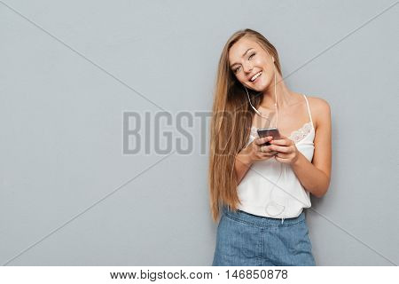 Young pretty cute girl with earphones listening music and holding smartphone isolated on a gray background