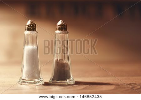Salt and pepper shakers on wooden table