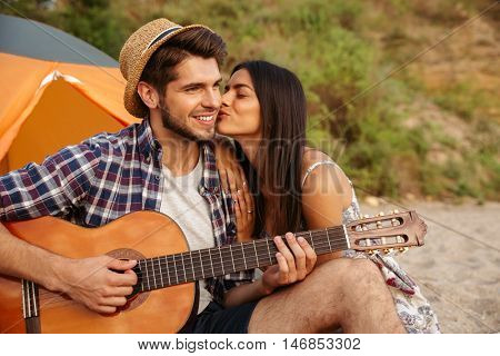 Portrait of a man playing guitar for his girlfriend sitting at the camping tent at the beach