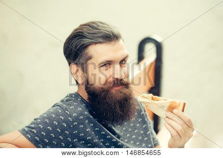 handsome sexy bearded young man hipster with long beard and mustache on smiling hairy face eating pizza sitting on street bench outdoor