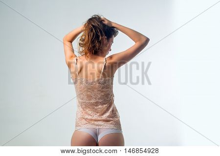 young woman with slim sexy body and buttocks has long hair in lace beige vest and panties standing in studio on grey background copy space