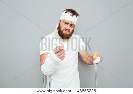 Angry bearded young man with crutches pointing on you over white background
