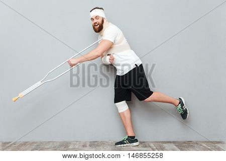 Happy funny young man posing and having fun with crutch over gray background