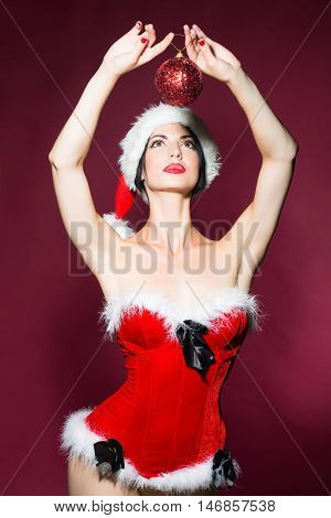 young sexy new year woman or girl with and red lips on pretty face in christmas santa claus hat and holiday costume holds decorative ball in studio on purple background