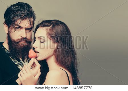 young sexy couple of woman with pretty face and brunette hair with bare shoulders and handsome bearded man with long beard eating red strawberry berry fruit in studio on grey background copy space